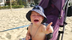 Baby girl is crying in stroller on the beach Stock Footage