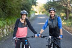 Biker couple with mountain bike on the road Stock Photos