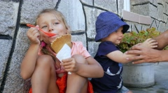Two children eating ice cream on summer street Stock Footage