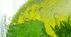 Sparkling bubbles water with a slice of lime. 4K macro footage, shot on RED Stock Footage
