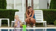 Mother and her little daughter walking near swimming pool Stock Footage