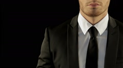Male model in stylish suite corrects his necktie Stock Footage