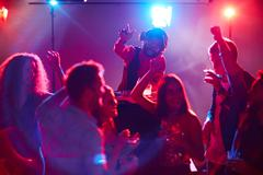 Ecstatic deejay enjoying disco party while young people dancing near by Stock Photos