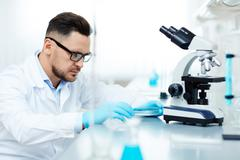 Young chemist analyzing new element in laboratory Stock Photos