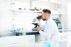 Contemporary scientist working with microscope in scientific laboratory Stock Photos