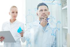 Serious chemist looking at chemical formula on transparent board with his assist Stock Photos