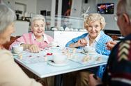 Senior friends playing lotto in free time Stock Photos