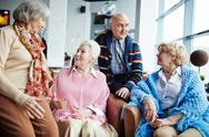 Aged adults having conversation indoors Stock Photos