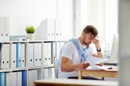 Tired businessman sitting by workplace in office Stock Photos