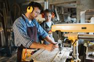 Carpenter in uniform and protective headphones working by drill machine Stock Photos