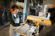 Female in uniform of carpenter using drill-machine in workshop Stock Photos