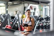 Smiling fit woman listening to music in gym Stock Photos