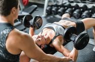 Strong woman with barbells exercising with trainer near by Stock Photos
