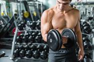 Muscular man exercising with barbell in gym Stock Photos