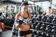 Sporty young female with metallic dumbbells Stock Photos