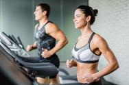 Happy woman runing on treadmill on background of man Stock Photos