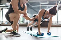 Trainer with stopwatch and young woman with dumbbells exercising on mat Stock Photos