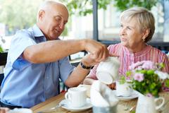 Senior man making tea to female in outdoor cafe Stock Photos