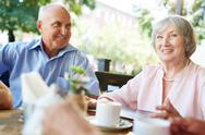 Aged man and woman spending time in cafe Stock Photos