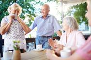 Several senior people sitting in outdoor cafe and talking Stock Photos