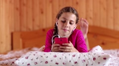Pretty girl lies on the bed and communicates via smartphone Stock Footage