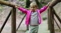 Little girl stands on a wooden bridge and does dance moves HD Footage
