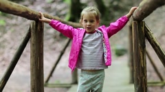 Little girl stands on a wooden bridge and does dance moves Stock Footage