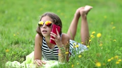 Pretty girl in sunglasses with red smartphone lies on the grass Stock Footage