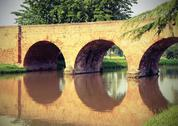 Ancient arched bridge made with red bricks with the river Stock Photos