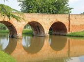 Antique arched bridge made of red bricks with the river Stock Photos