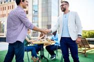 Two young businessmen handshaking outdoors Stock Photos