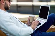 Modern guy typing on laptop outdoors Stock Photos