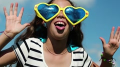 Funny girl in big glasses in shape of hearts looks at the camera and makes faces Stock Footage