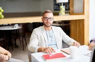 Serious businessman looking at camera at workplace Stock Photos