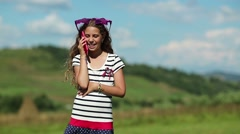 Beautiful girl stands on the meadow and speaks on cell phone Stock Footage