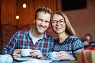 Happy couple with drinks looking at camera in cafe Stock Photos