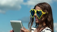 Merry girl in big sunglasses in the shape of hearts communicates via tablet pc Stock Footage