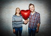 Young couple with red heart-shaped balloon looking at camera Stock Photos