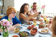 Young friends sitting by table on Thanksgiving day Stock Photos