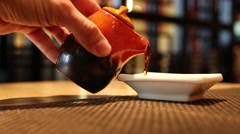 Man in japanese restaurant pours soy sauce Stock Footage