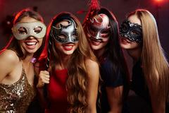 Group of happy girls in masquerade masks having party Stock Photos