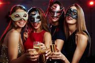 Girls in masks toasting with champagne at party Stock Photos