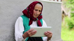 Old woman with tablet pc communicates through skype Stock Footage