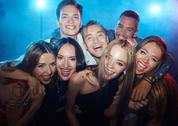 Group of ecstatic friends laughing at party in nightclub Stock Photos