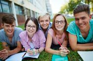 Cheerful friends lying on campus lawn Stock Photos