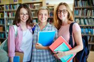 Friendly girls with books looking at camera Stock Photos