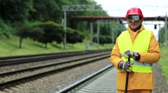 Railway worker in yellow uniform with crowbar in hands stands near railway line Stock Footage