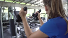Young woman building triceps and biceps at gym Stock Footage