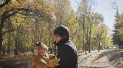 Happy family Dad throws child son up on a walk in the autumn leaf fall in park Stock Footage
