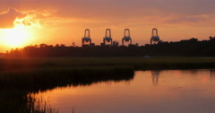 Industrial Cranes at Sunset with Marsh and Boat Stock Footage